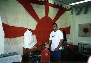 Charles and Austin in front of a Japanese commanders flag.